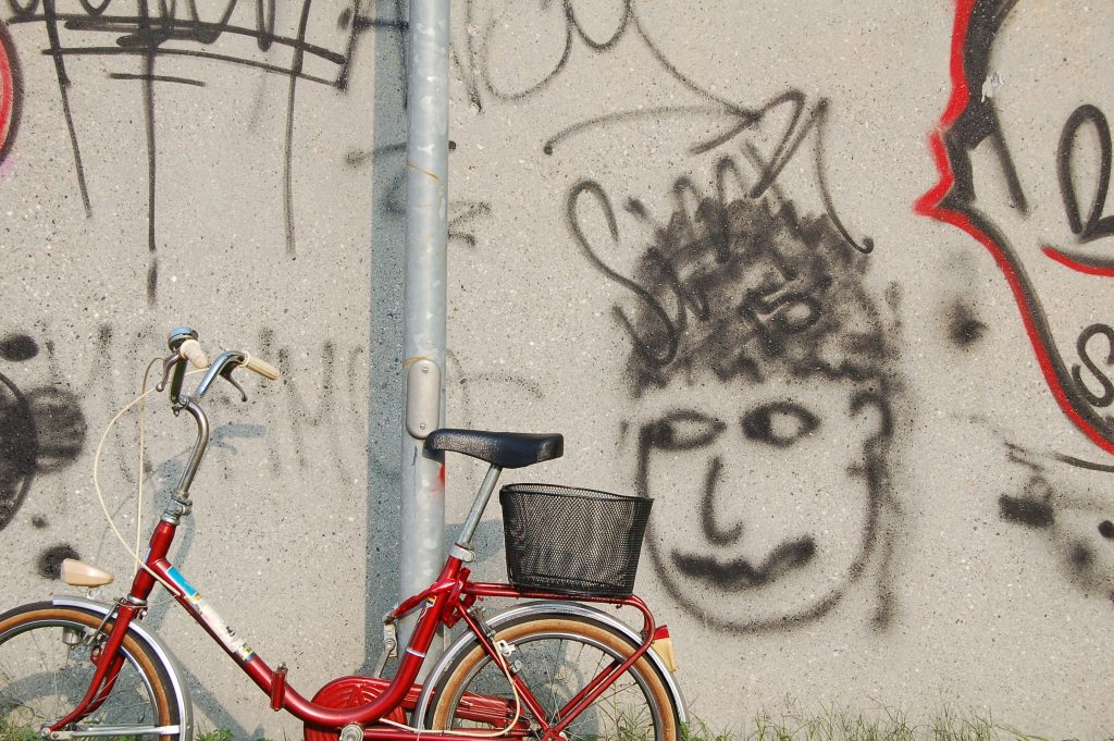 Photograph of a bicycle in front graffitied wall