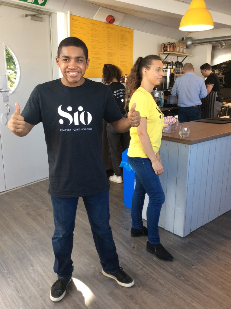 Photograph of a young man with his thumbs up in a coffee shop