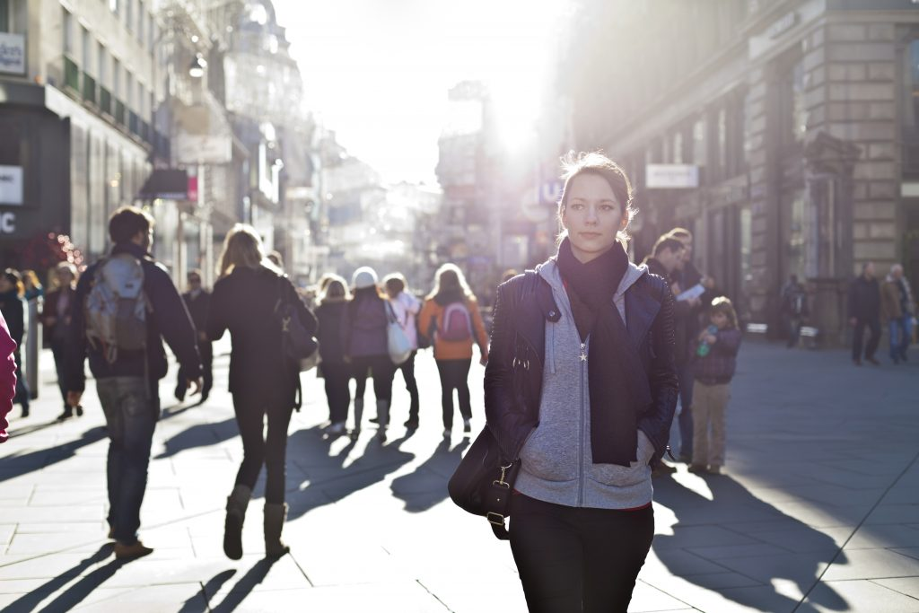 Woman walking alone down a busy street