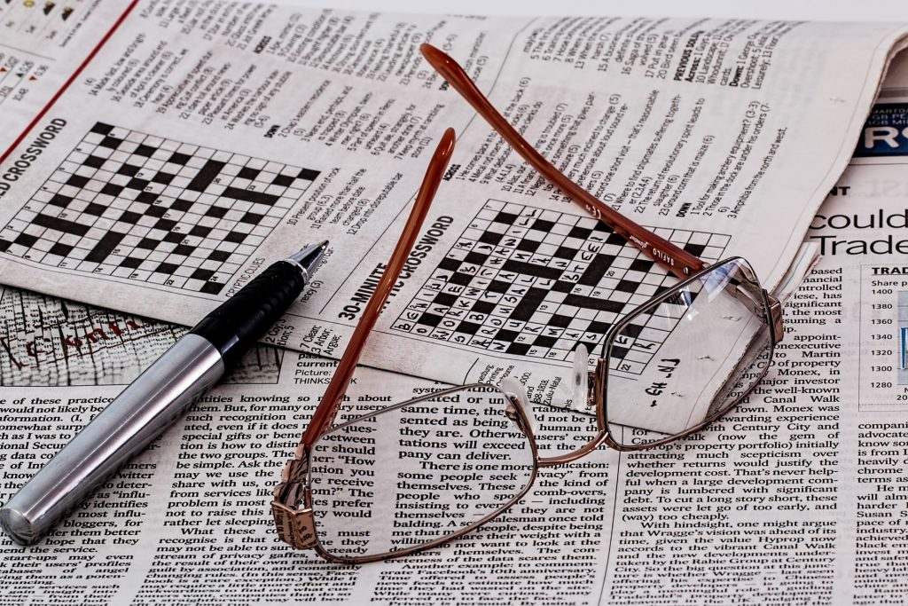 pen and glasses resting on a newspaper crossword