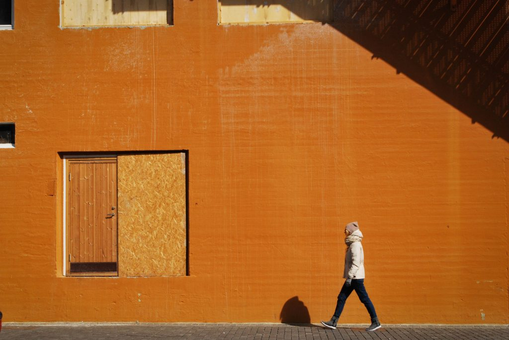 person walking in winter coat beside a bright wall