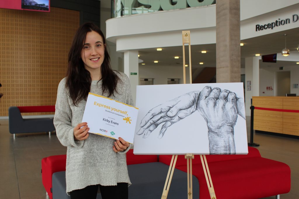 Artist Kirby Evans with certificate and artwork