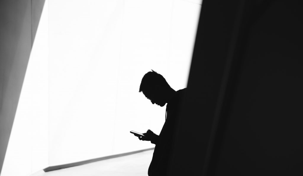 silhouette of young man using a phone