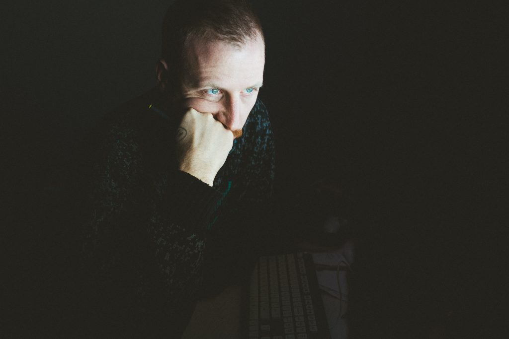 man sat in dark lit by screen