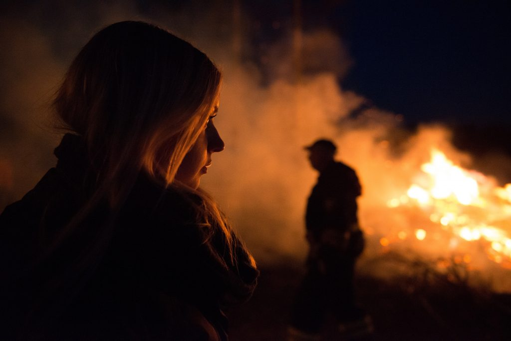 woman watching bonfire