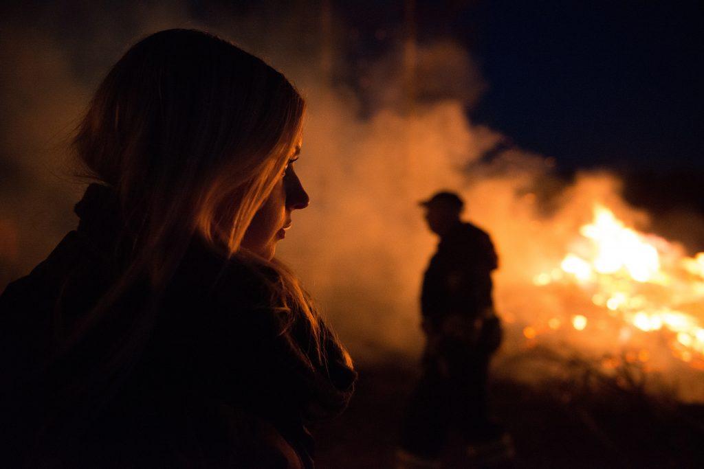 woman watching bonfire