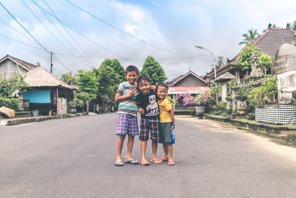 Balinese children standing in the street smiling at the camera