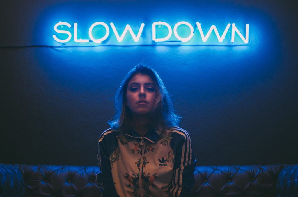 woman sitting beneath a neon sign that says slow down