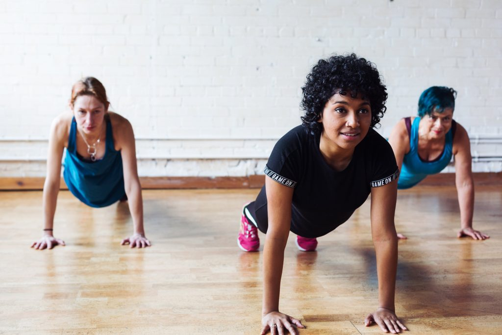 three woman in a yoga class