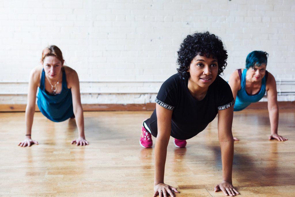 three woman in a yoga class