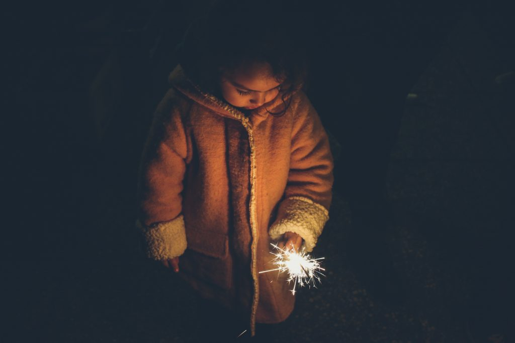 child in winter coat holding a sparkler