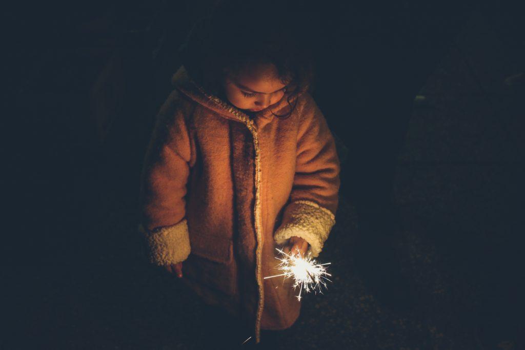 child in winter coat holding a sparkler