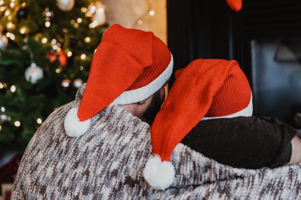 two people in santa hats sat under a blanket