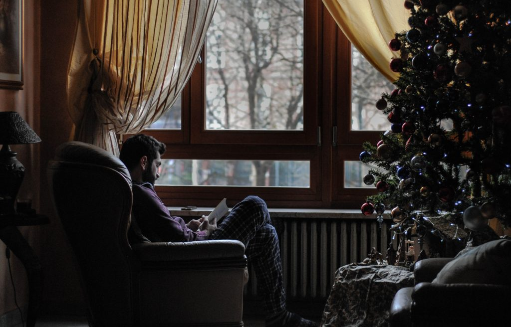 man sitting alone next to christmas tree