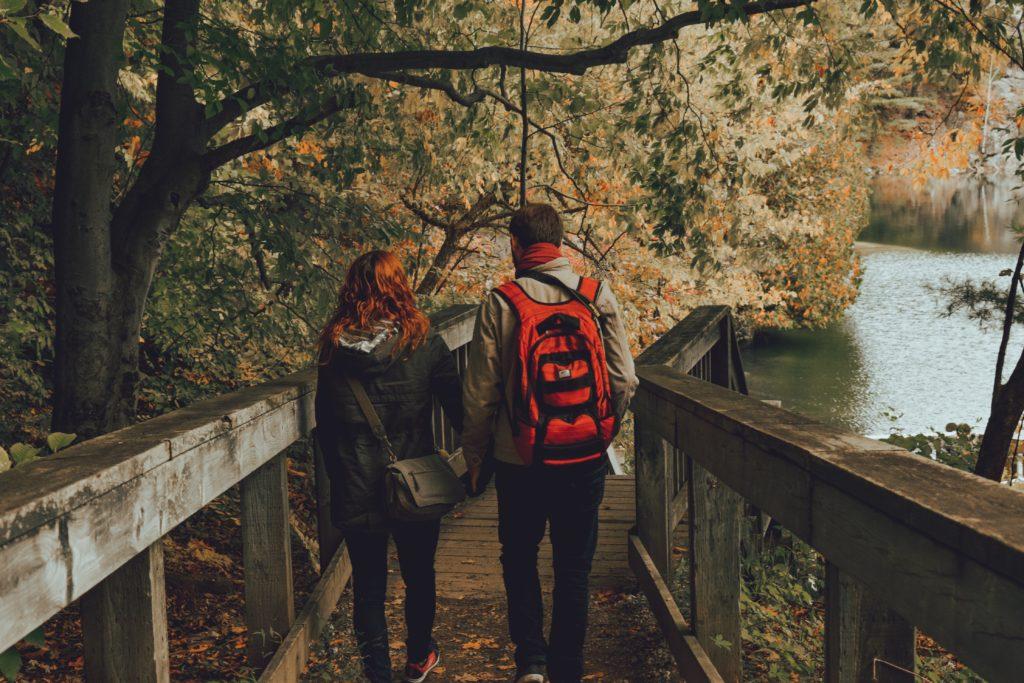 man and woman walking on bridge near water
