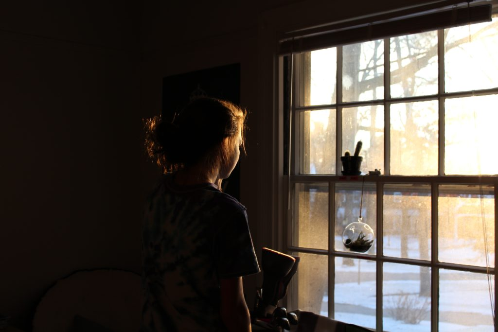 woman looking out of window from dark room