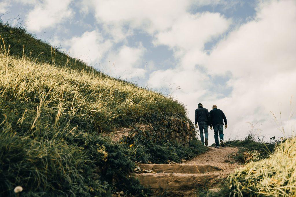 men walking on grassy hill
