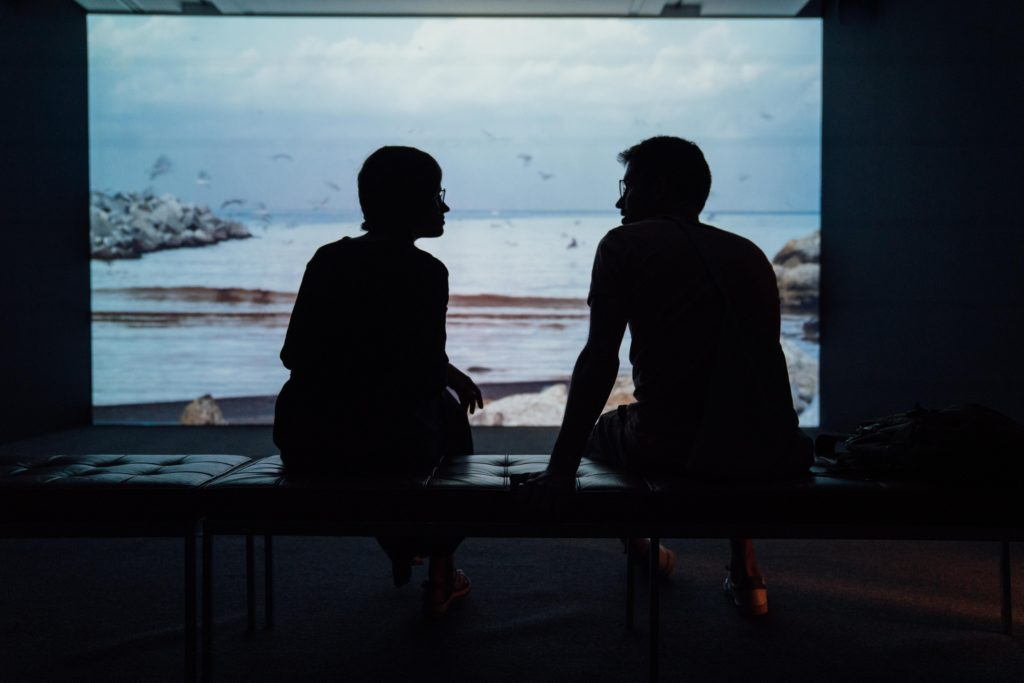 two people silhouetted against a bright screen