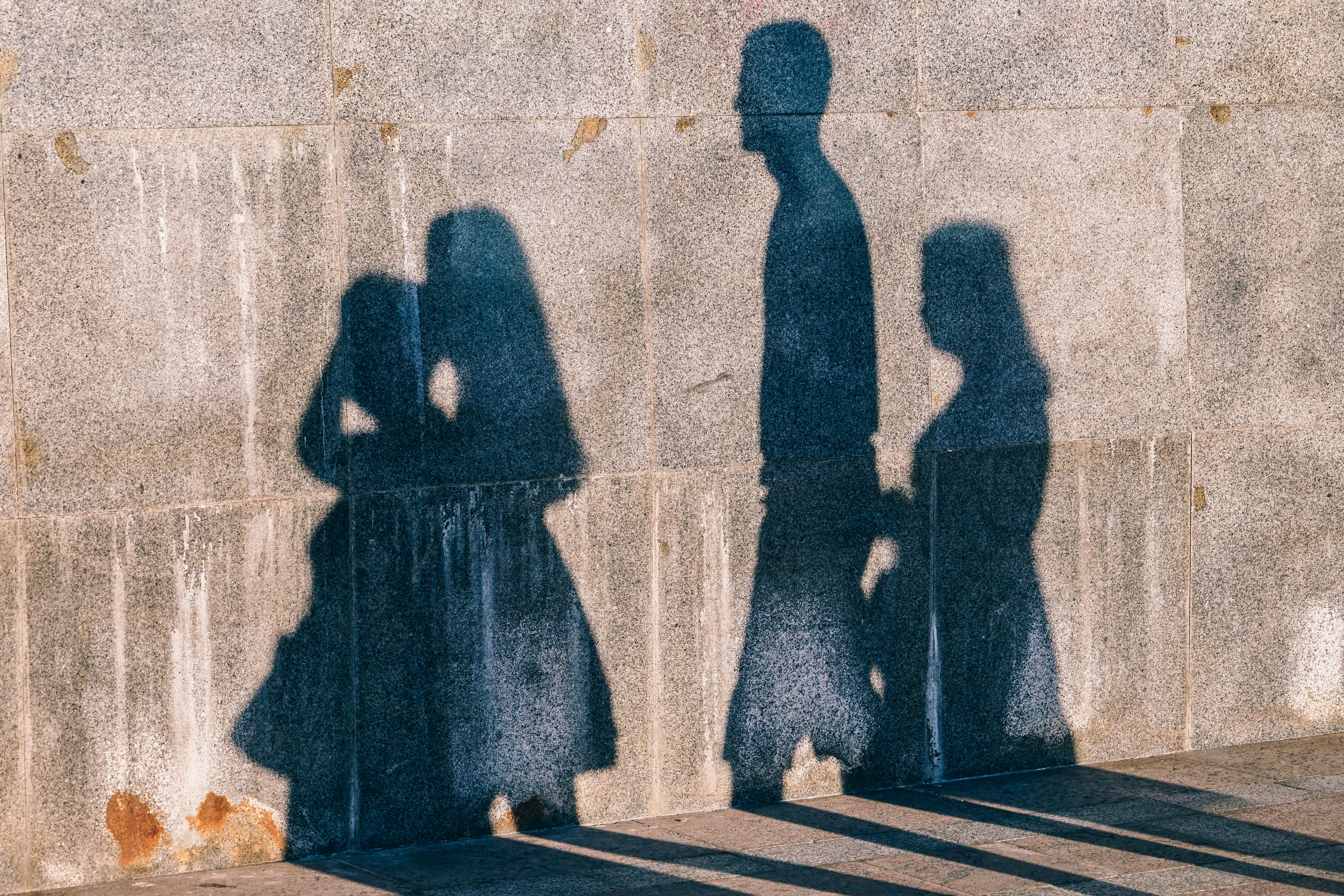 children's shadows on a grey wall