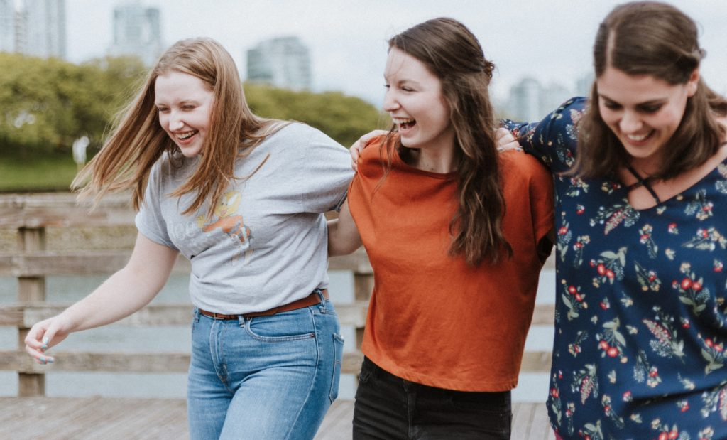 three women linking arms and laughing
