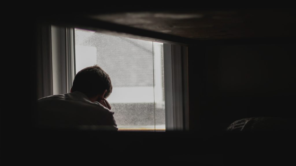 man in a dark room looking out a gloomy window