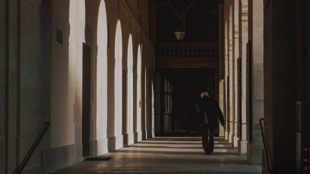 An older man walks down a shadowy corridor