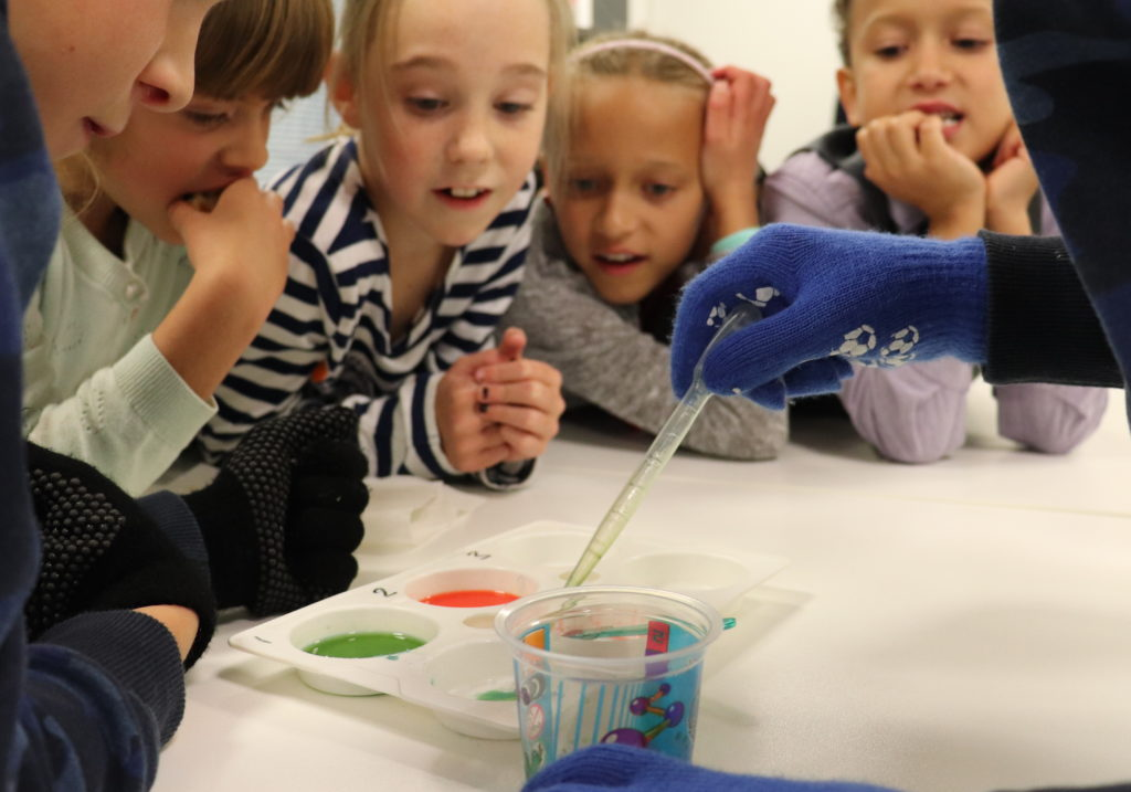 children watch adult conduct colourful experiment