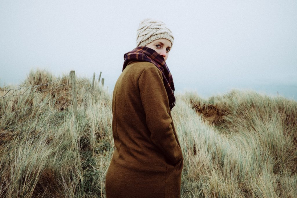 woman walking in winter hat and coat in sand dune