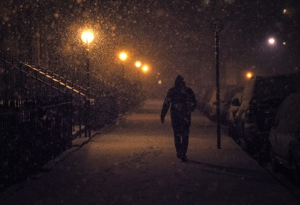 man walking in snow in dark