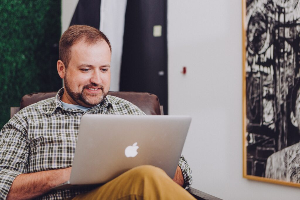 a white man with a beard using a laptop balanced on his lap