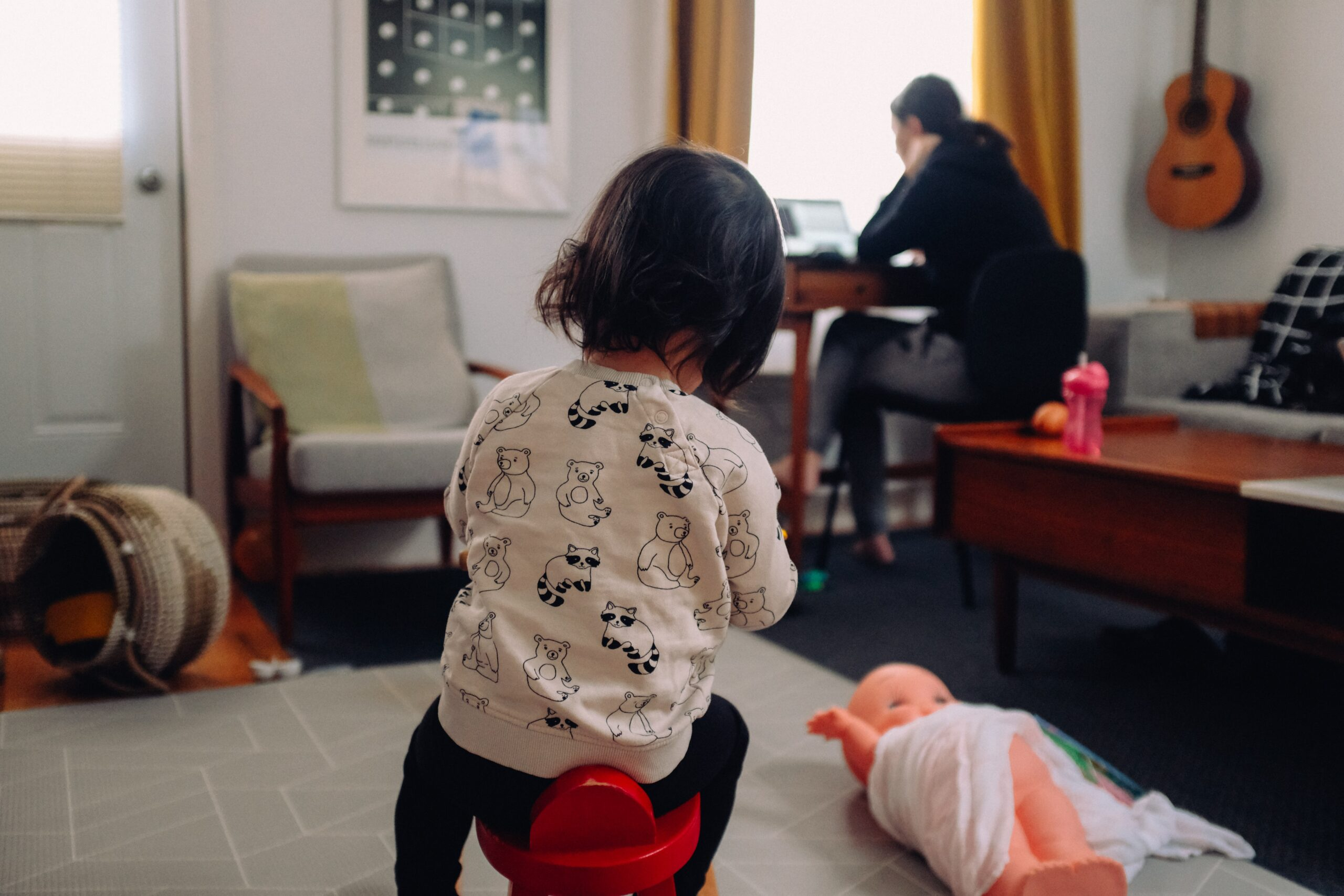 a child sits on a stool next to some toys while an adults works at a laptop