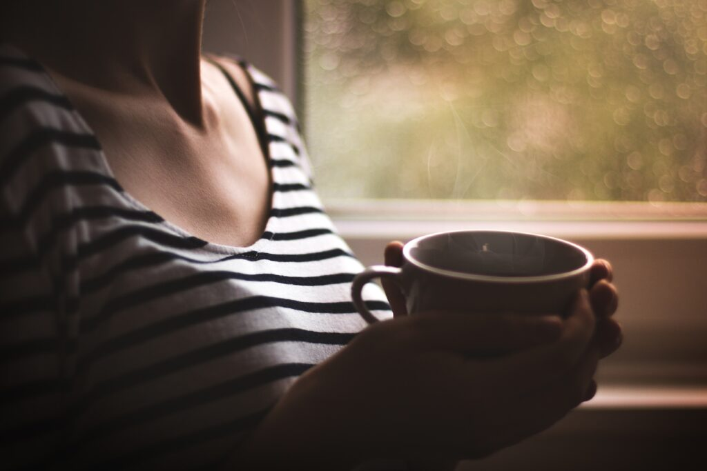 white woman drinking tea by window