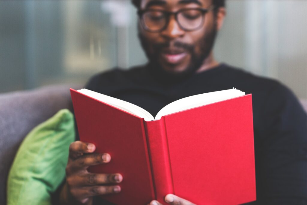 young black man reading red book