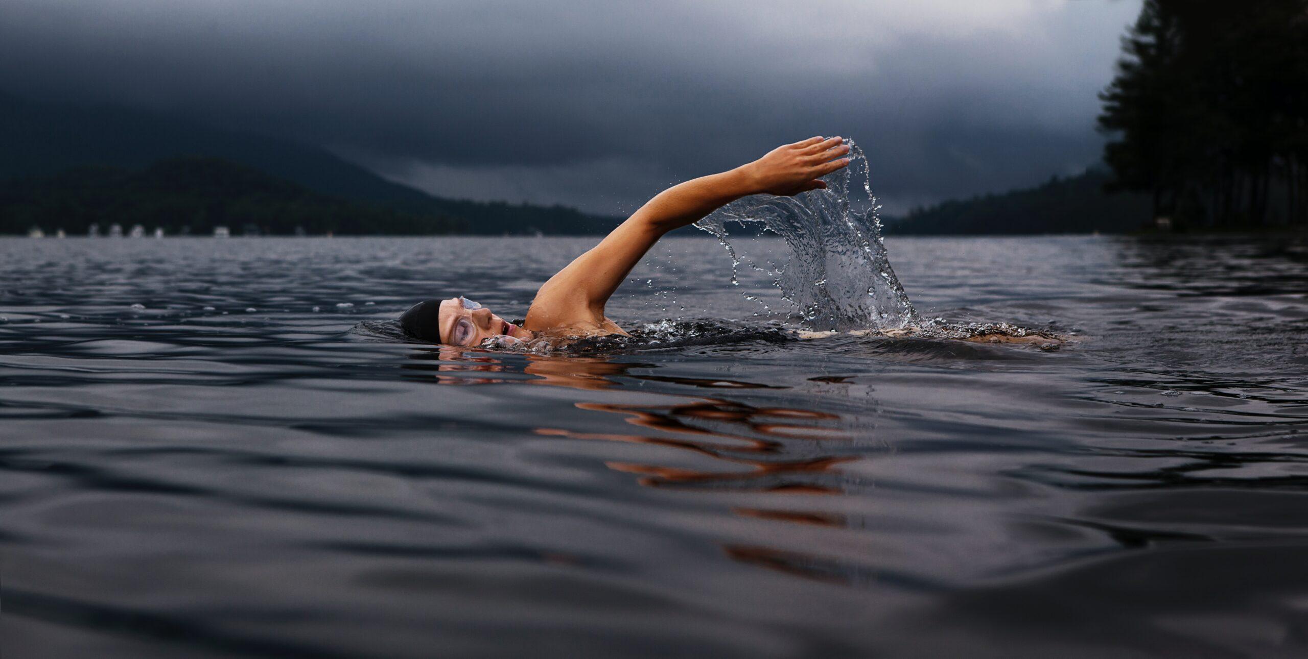 woman in swim cap swimming in water