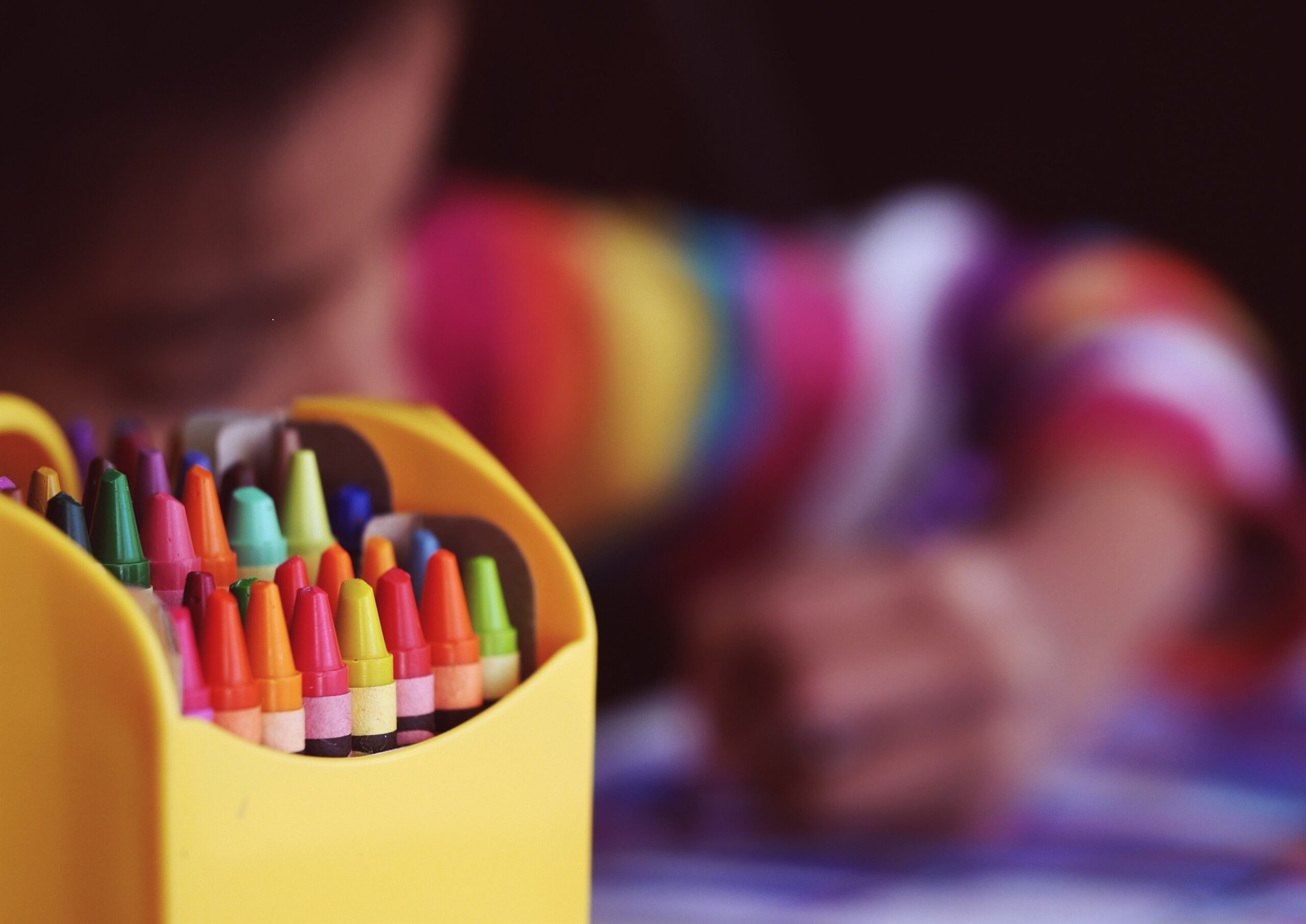 a box of bright coloured crayons sits in front of children colouring