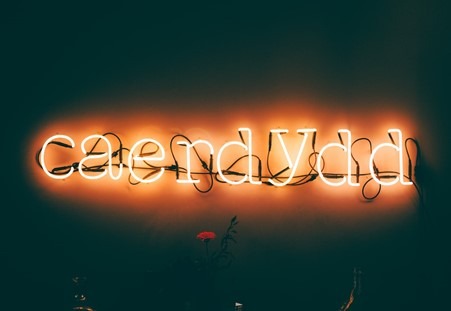 the welsh name for cardiff (caerdydd) written in neon lights on a black background
