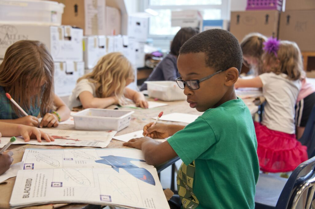 a young black boy writing in a workbook in a class of children