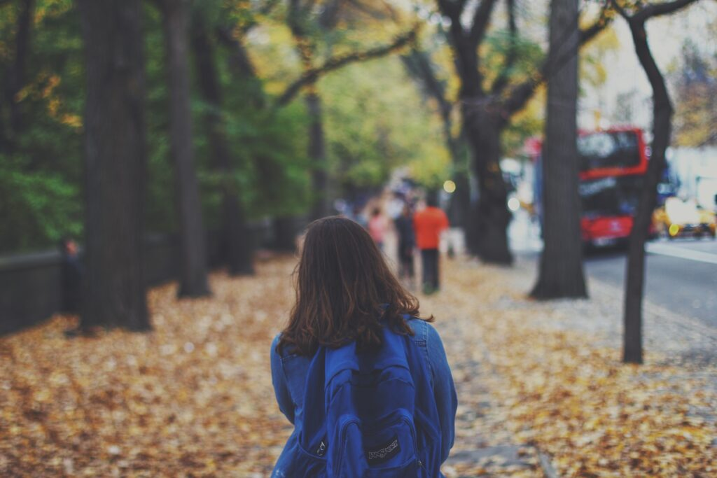 a young girl walking along a pavement covered in autumnal leaves