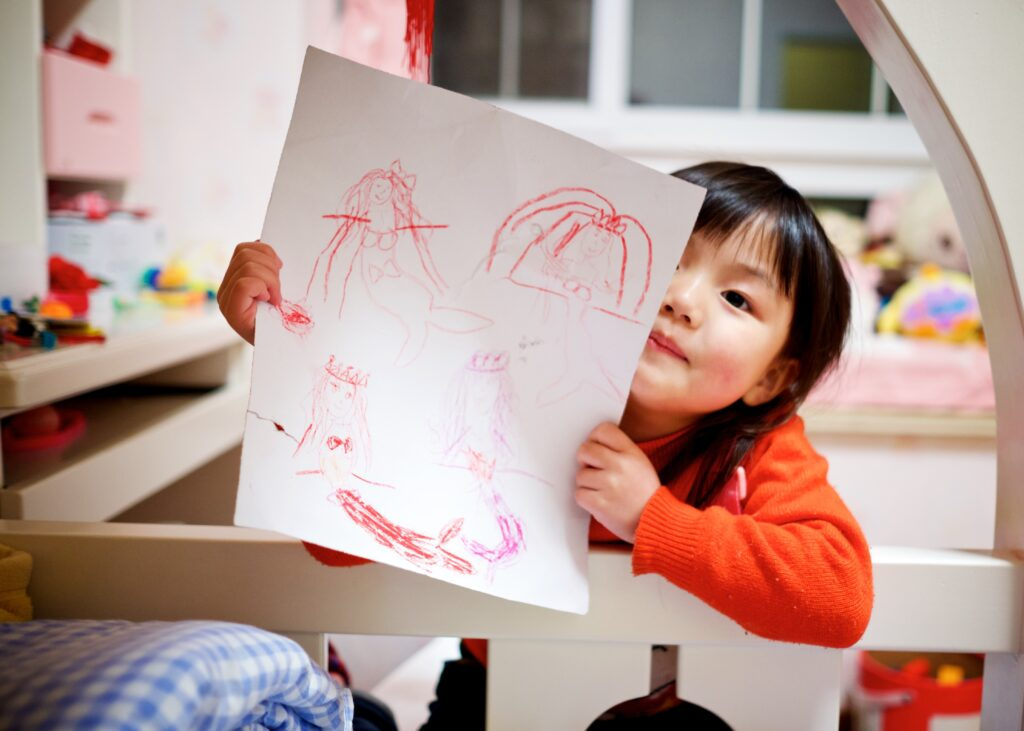 little girl showing a page of drawings