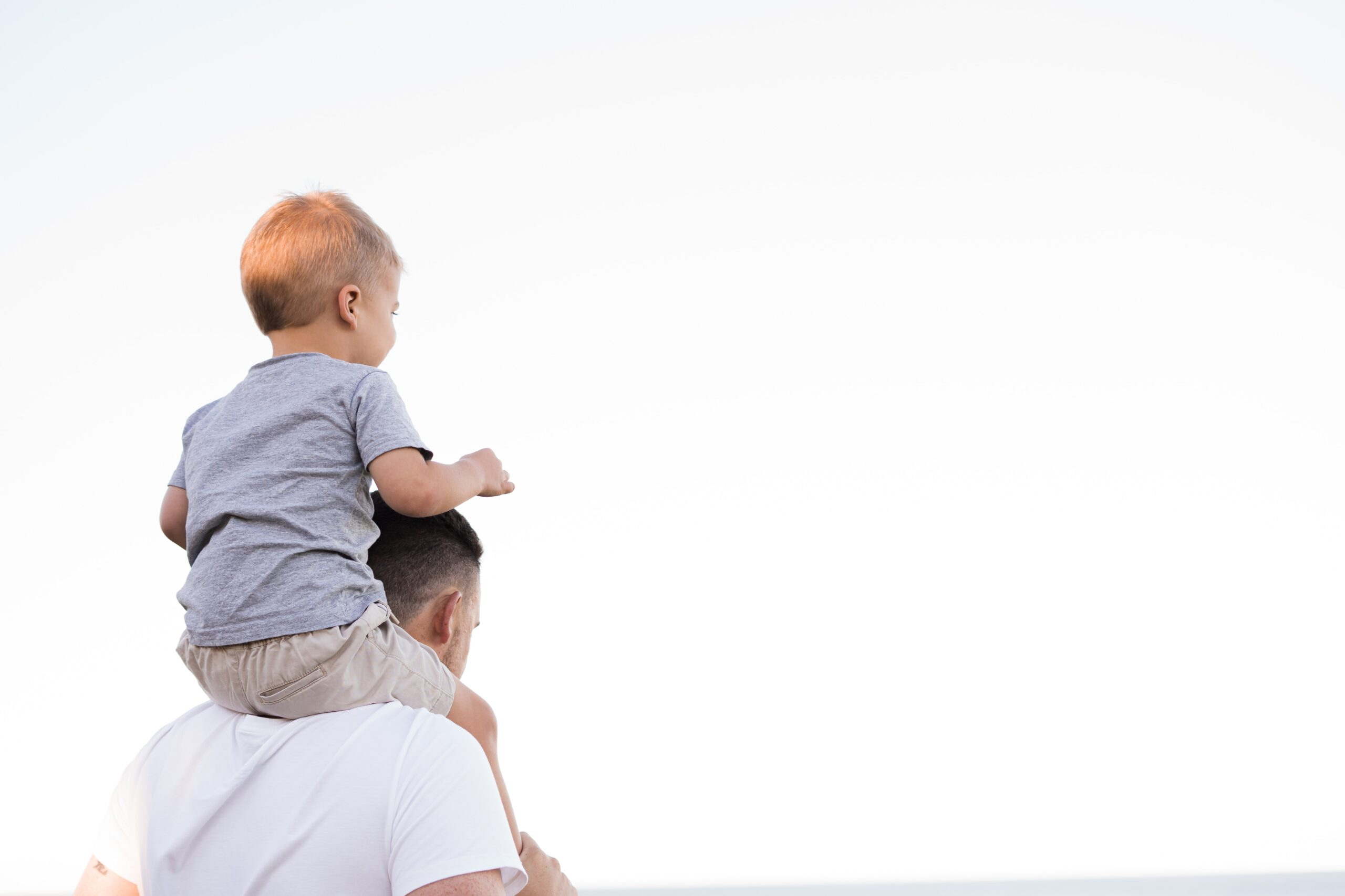 a young child sits on adult's shoulder against white backdrop