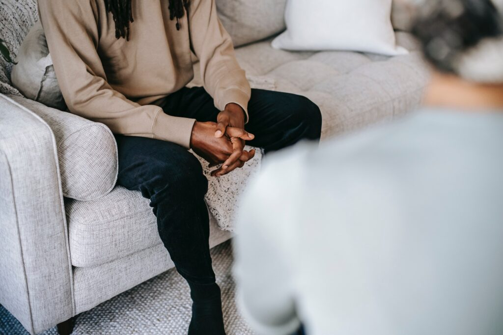 young black man sitting on sofa speaking to someone whose back is to the camera