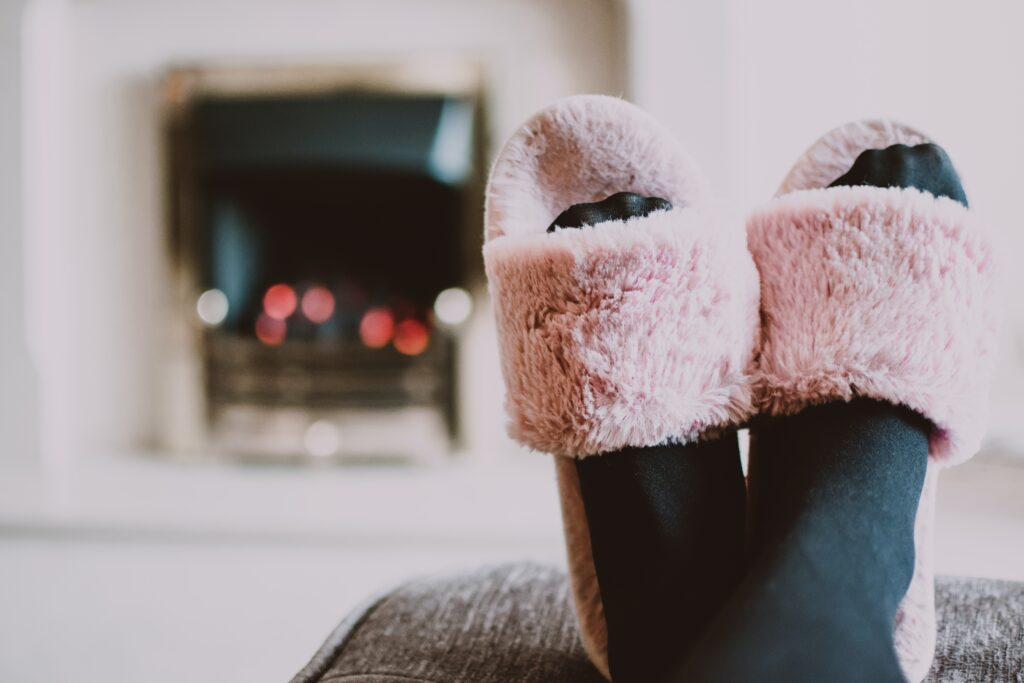a pair of feet wearing pink slippers in front of a fire