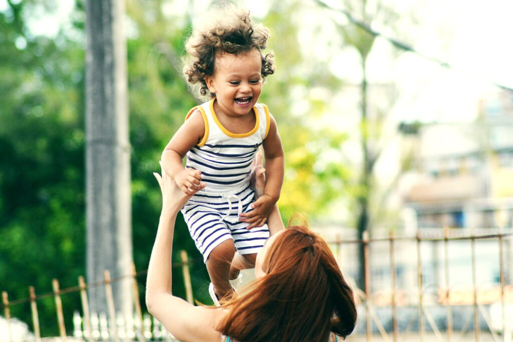 a child laughing and being thrown int the air