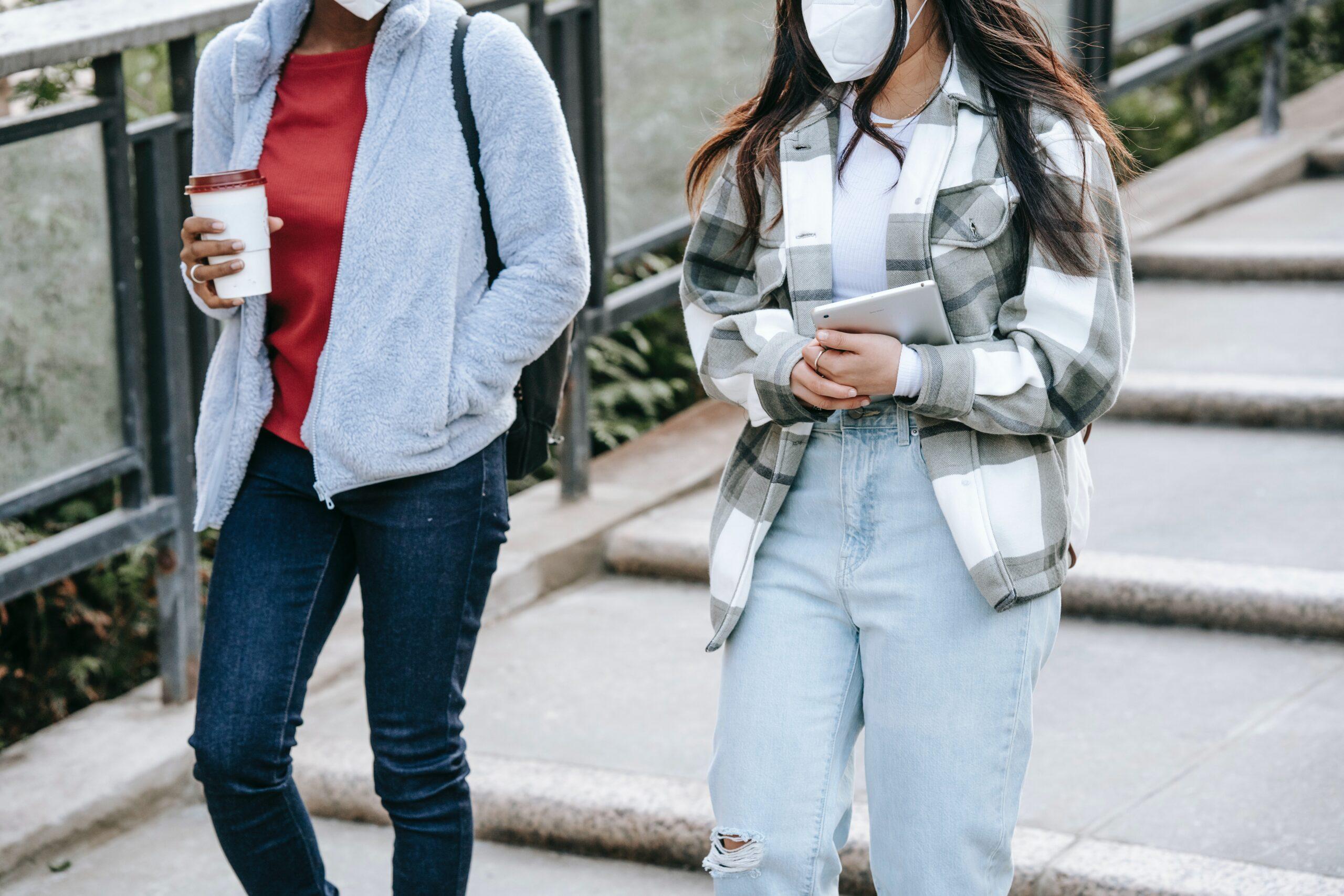 2 women walk wearing masks and holding a takeaway coffee