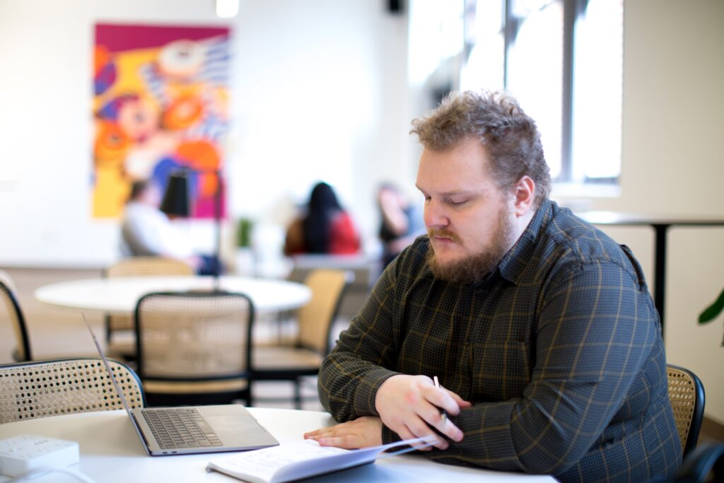 young white man with beard sat at table making notes in a book
