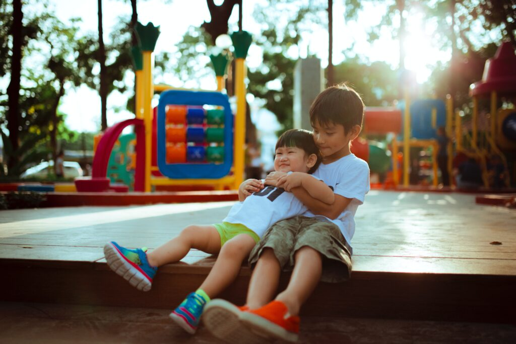 two little boys hugging in a playground