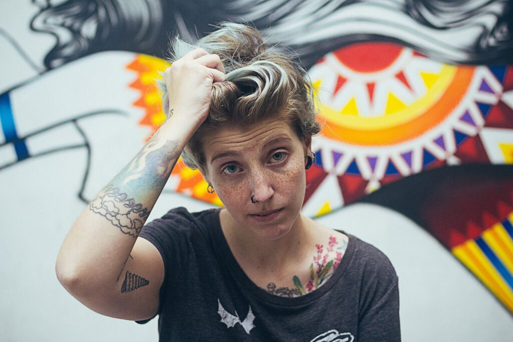 white person with a hand in their short light hair looking at the camera in front of a bright graffiti background