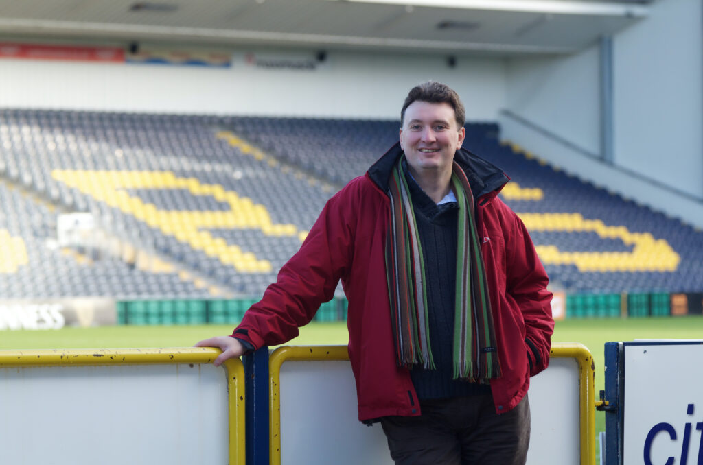 ncmh director Ian Jones standing in a football stadium in a red coat and stripy scarf